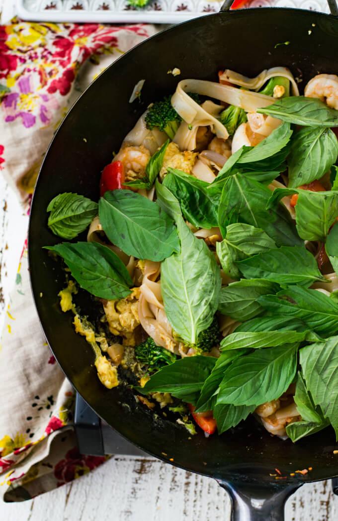 A wok of Thai Drunken Noodles with Thai Basil leaves sprinkled on top.