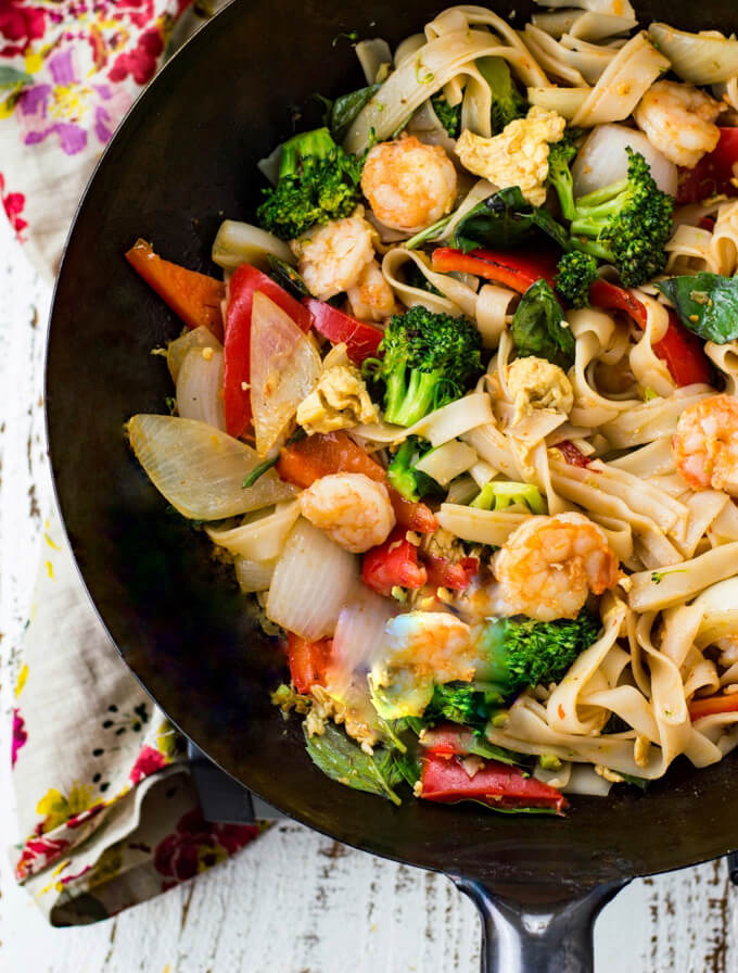 A wok of Thai Drunken Noodles with broccoli, red peppers and onions.