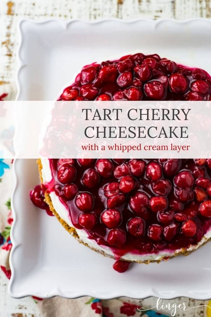 A top view of a cherry cheesecake on a white cake stand. A colorful napkin sits next to it.