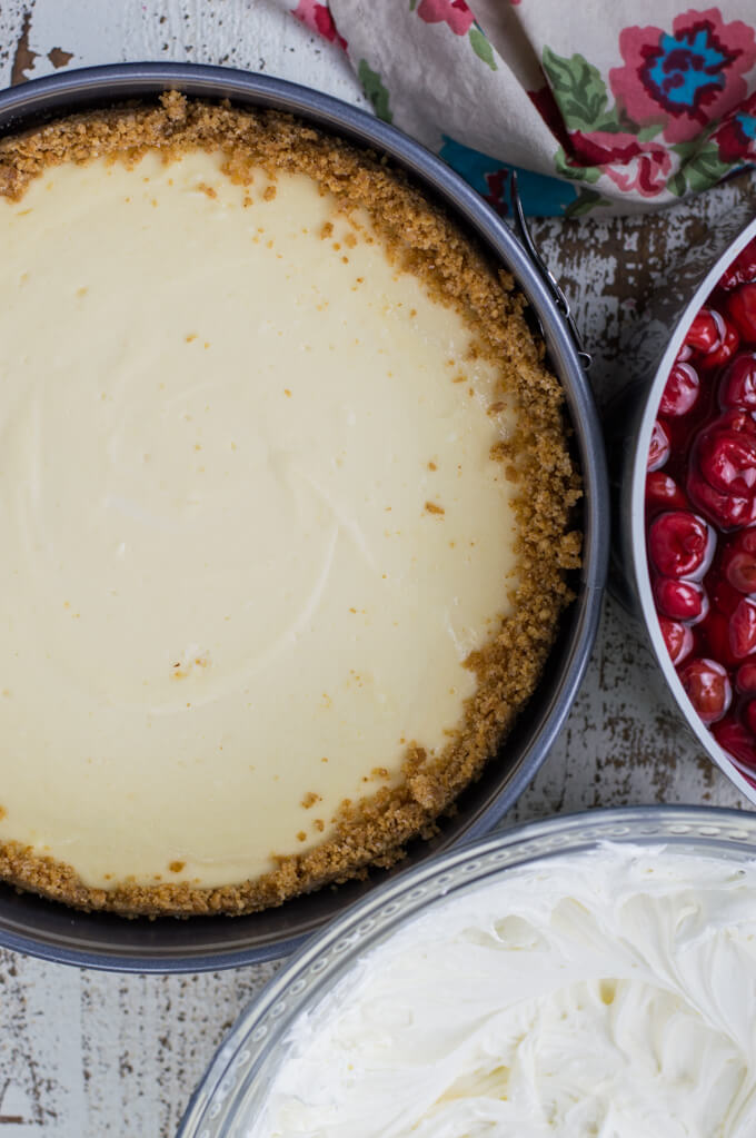 A baked cheesecake in a springform pan with a pan of cherry pie filling and cool whip filling sits next to the pan.