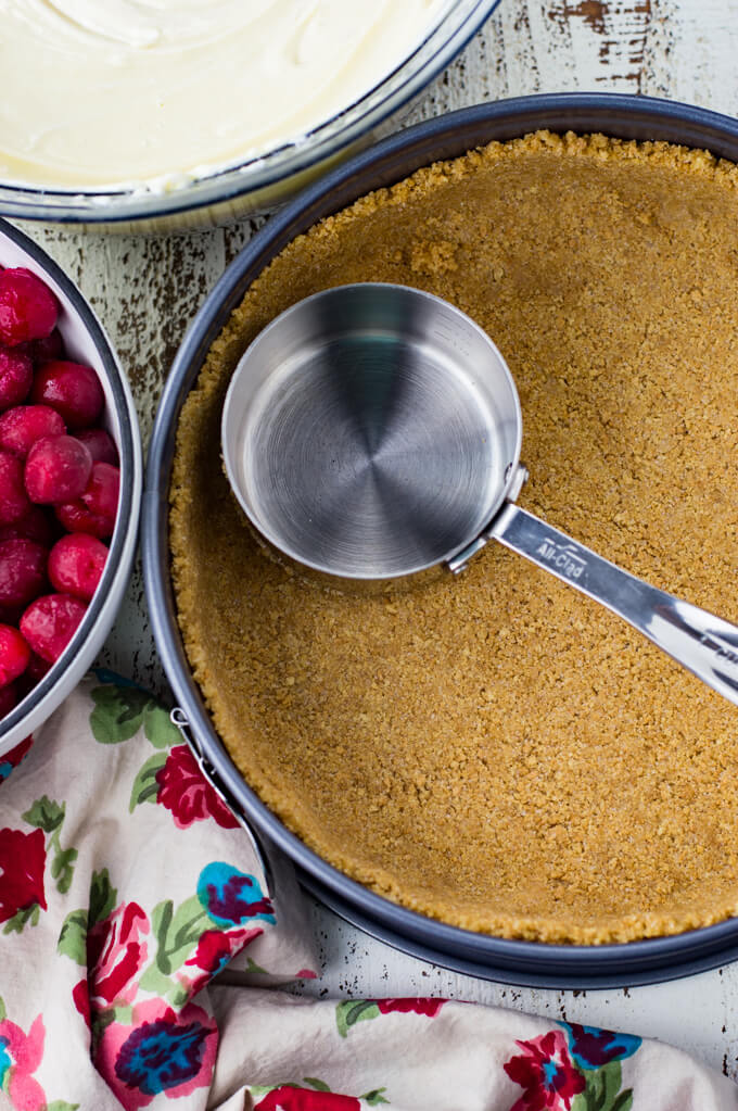 A springform pan with a graham cracker crust. A metal measuring cup sits on the crust. A bowl of cherries, a red flowered napikin and a bowl of cheesecake filling sits next to the pan.