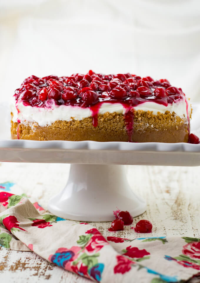 A cherry Cheesecake sits on a white cake plate. Three cherries and a colorful napkin sit down underneath the plate.