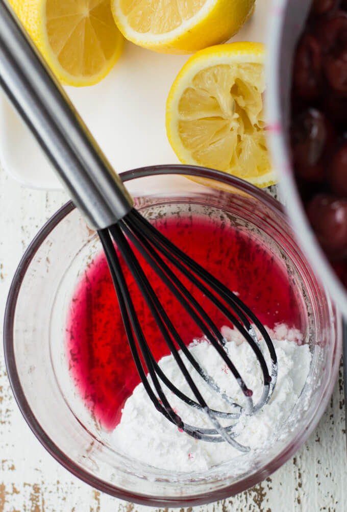 A small bowl of cherry juice with cornstarch. A small whisk sits in the bowl. Squeezed lemons and a pan of cherries sit next to the bowl.