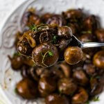 A spoonful of sautéed mushrooms are above a bowl of the same.