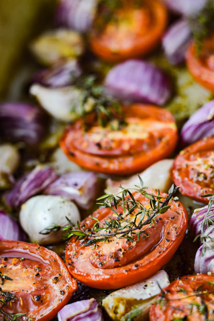 Tomatoes, garlic and red onions and sprigs of thyme are in a stoneware baking pan.