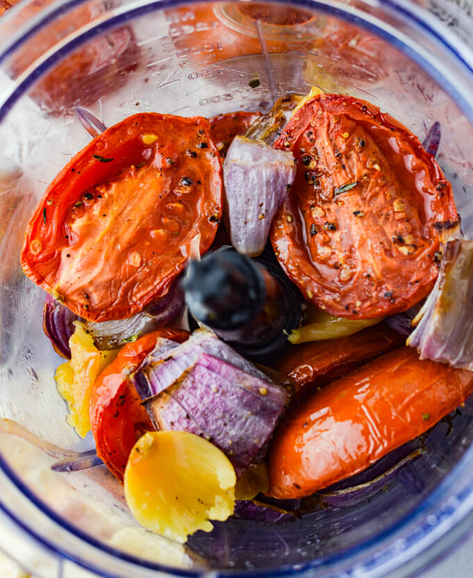 Roasted tomatoes, garlic and red onions are in a food processor.