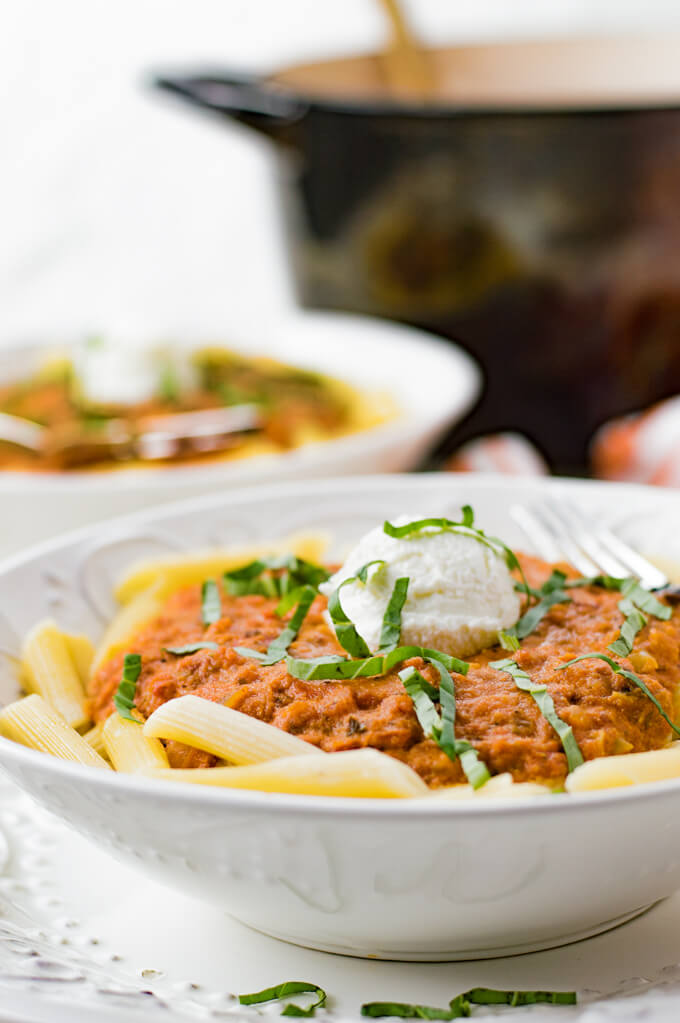 Vodka Pasta Sauce sits on top of penne pasta with a dollop of ricotta cheese and julienned basil leaves are scattered on top. A pan of the sauce and another bowl is blurred in the background.